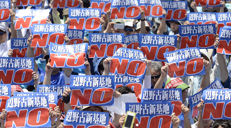ARCHIVE PHOTO: Protesters raise placards during a rally to oppose the transfer of a key U.S. military base within the prefecture, at a baseball stadium in the prefectural capital Naha on Japan's southern island of Okinawa, May 17, 2015. © Kyodo