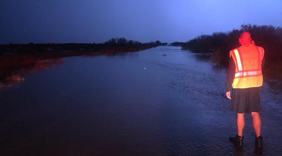 Arizona Highway 238 washed out by flooding near mile marker 26, illuminated by lightning