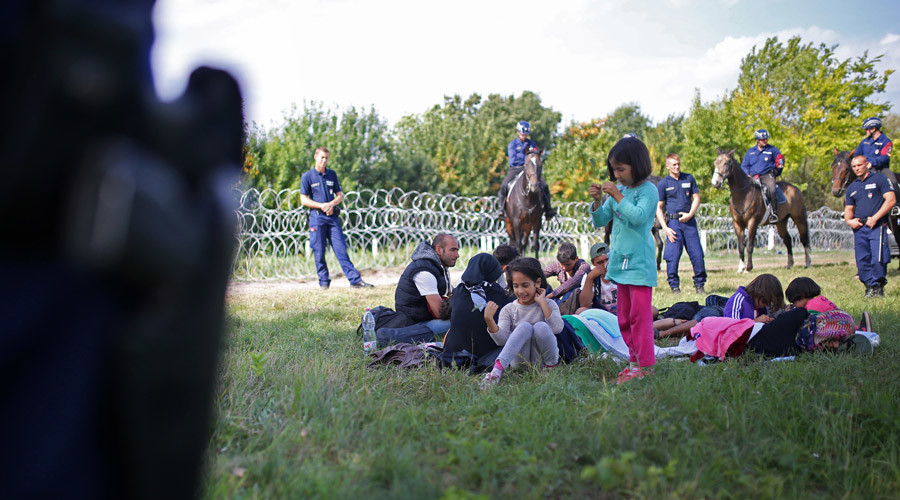 Migrants guarded by Hungarian police sit on the field after being detained for illegal crossing from Serbia to Hungary near the village of Asotthalom, September 16, 2015. © Dado Ruvic