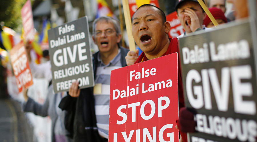 Protestors demonstrate as the Tibetan spiritual leader, the Dalai Lama speaks with the former Bishop of Canterbury Lord Williams during a dialogue session at Magdalene College in Cambridge, Britain September 16, 2015. © Darren Staples