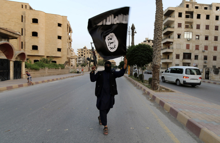 A member loyal to the Islamic State in Iraq and the Levant (ISIL) waves an ISIL flag in Raqqa, Syria. ©Stringer