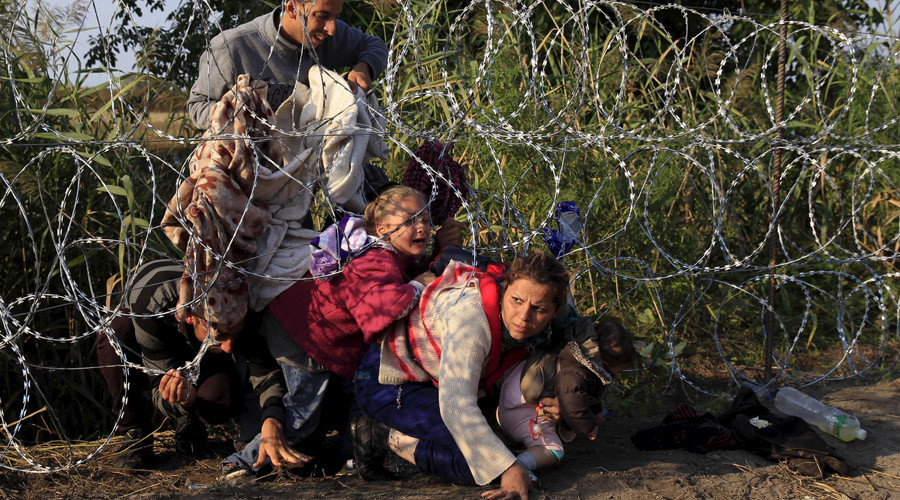 Syrian migrants cross under a fence as they enter Hungary at the border with Serbia, near Roszke. © Bernadett Szabo