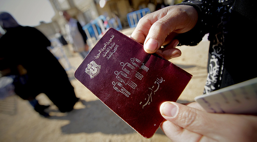 A Syrian woman shows her passport as families wait to be registered by the UNHCR in Lebanon © Joseph Eid