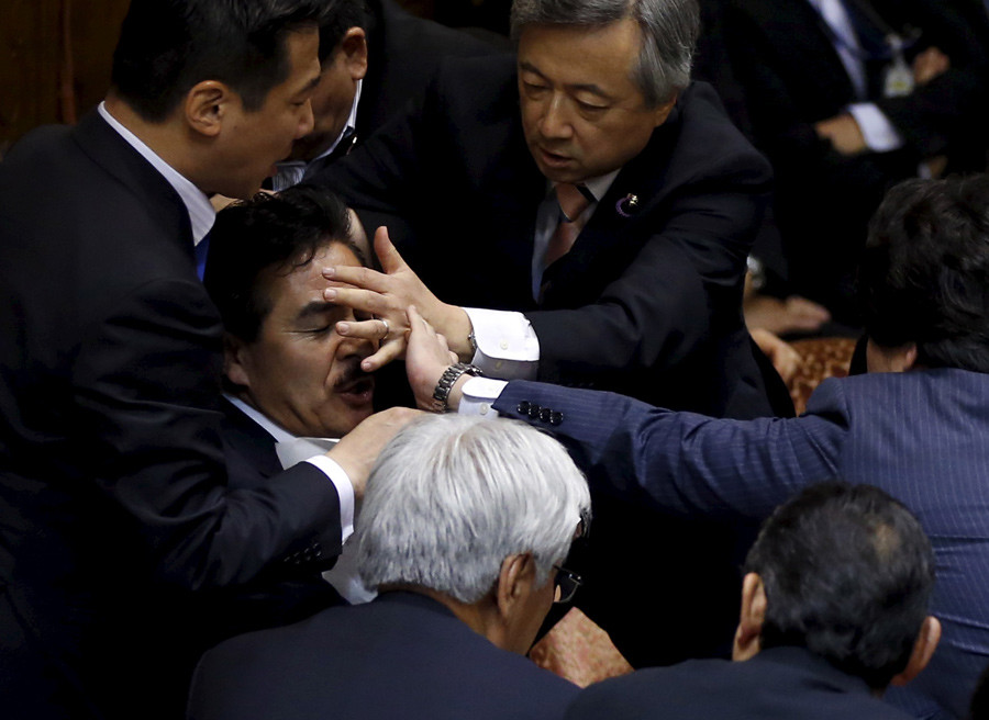 Opposition lawmakers crowd around Masahisa Sato (2nd L), deputation chairman of the upper house special committee on security at the parliament in Tokyo, Japan, September 17, 2015. © Toru Hanai