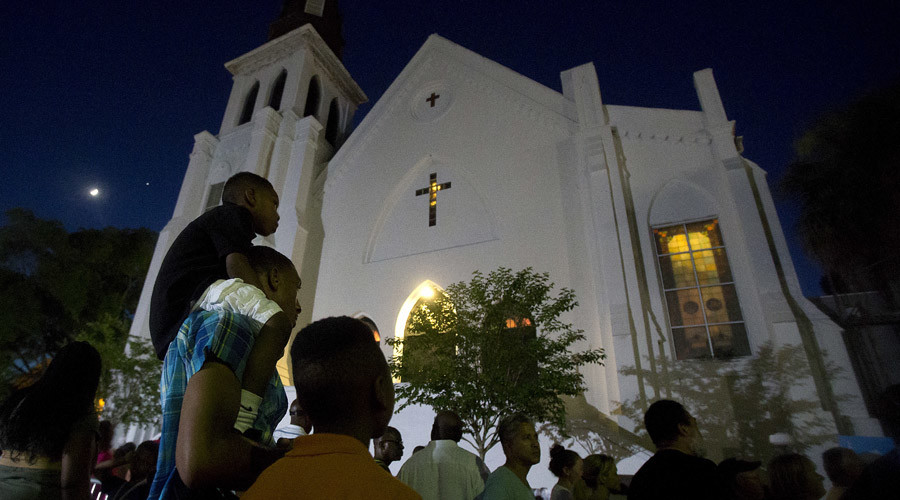 A father carries his son on his back as they listen to gospel music being sung during a vigil outside Emanuel African Methodist Episcopal Church in Charleston, June 20, 2015. © Carlo Allegri