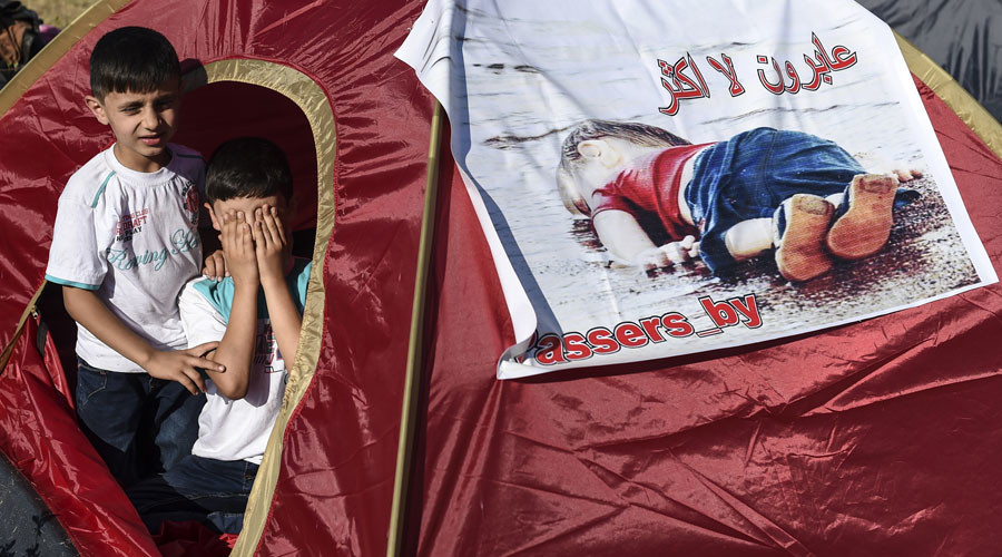 Children sit inside a tent bearing an image of three-year-old Aylan Kurdi, the Syrian toddler who's body washed up on a beach in Turkey, as Syrian migrants gather near the highway on the way to the Turkish-Bulgarian border at Edirne on September 15, 2015, in Edirne.  © AFP Photo