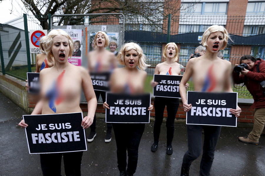 Topless activists of women's rights group FEMEN stage a protest in front of the polling station where France's far-right National Front leader Marine Le Pen will cast her ballot in Henin-Beaumont, northern France, March 29, 2015. © Pascal Rossignol