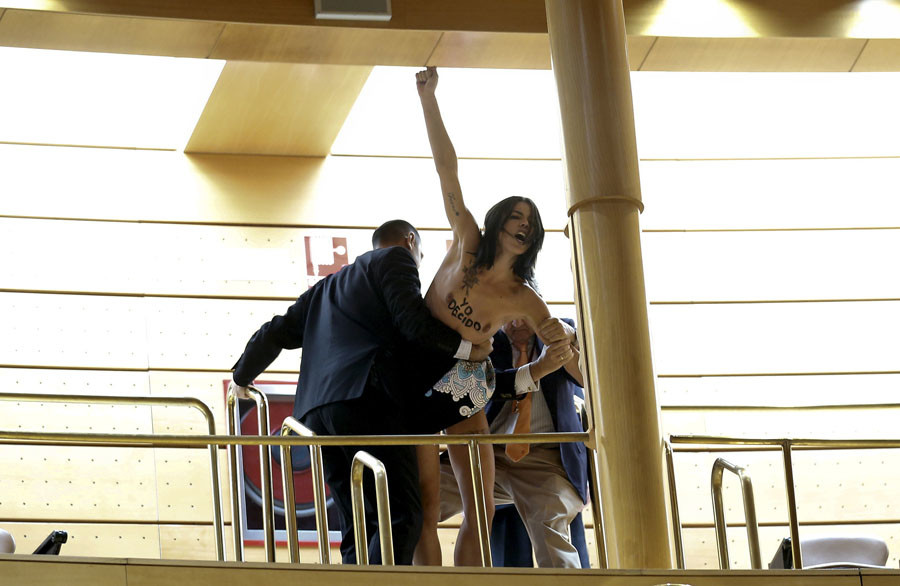 A topless activist from the feminist movement Femen is grabbed by senate janitors as she protests against the restriction of abortion for women under 18 without their parents' consent, during a session at the senate in Madrid, Spain, September 9, 2015. © Andrea Comas