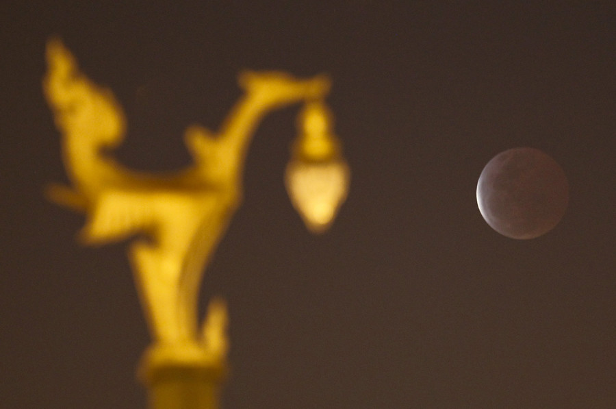 "A total lunar eclipse, also known as a ""blood moon"", is seen from near a swan statue in Nakhon Pathom province on the outskirts of Bangkok April 4, 2015. © Chaiwat Subprasom"