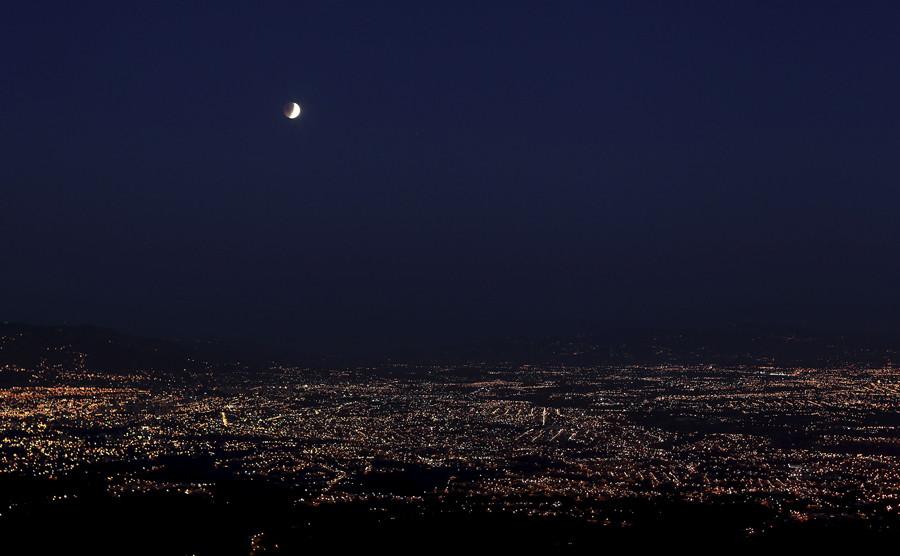 A lunar eclipse is seen over San Jose city in Rancho Redondo April 4, 2015. © Juan Carlos Ulate
