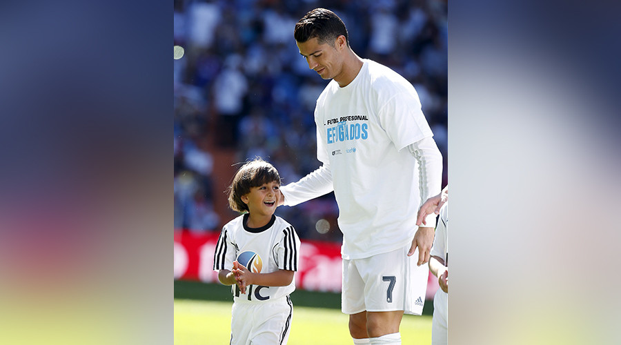 A Syrian refugee boy who was filmed being tripped by a camerawoman as he fled police in Hungary with him, smiles as he stands next to Cristiano Ronaldo before the Spanish first division soccer match against Granada at Santiago Bernabeu stadium in Madrid, Spain, September 19, 2015 © Sergio Perez