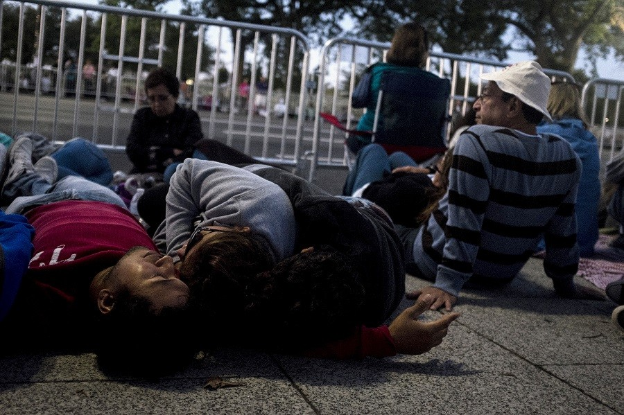 A family sleeps before sunrise along Pope Francis' parade route on Constitution Avenue