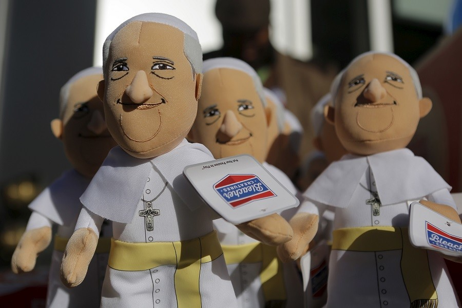 A man sells Pope Francis dolls on a street corner during the pope's visit