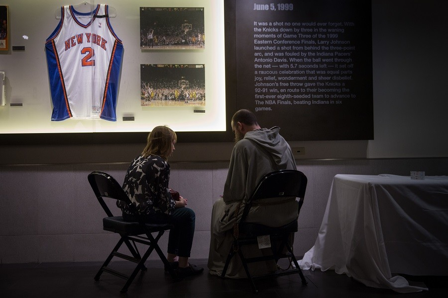 A priest hears a confession from a woman in the hallways of Madison Square Garden