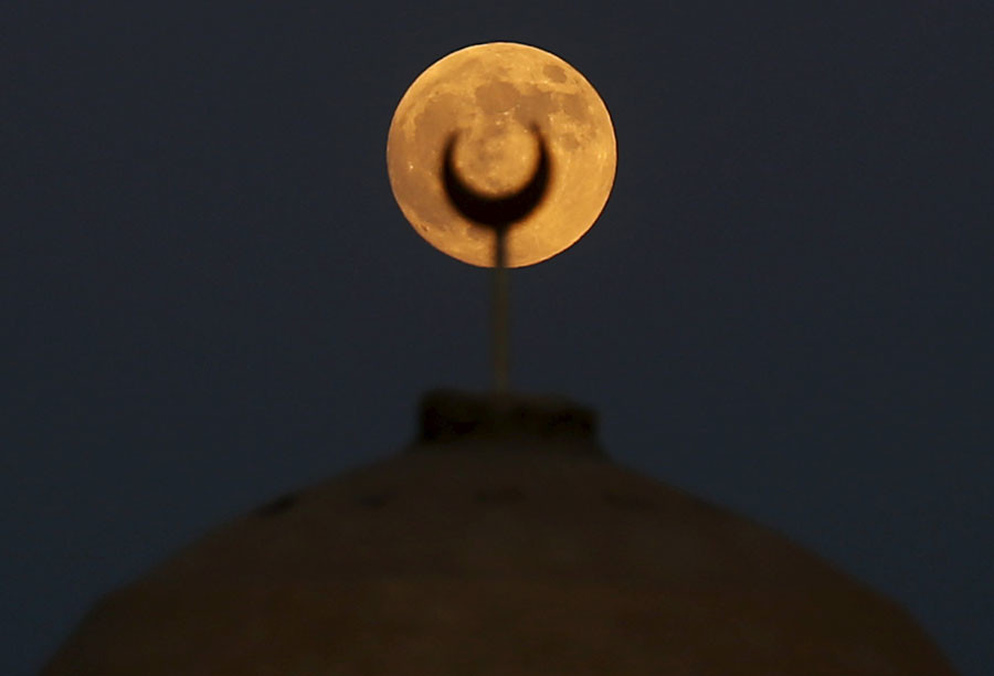 A supermoon, the last of this year's supermoons, rises over a minaret of a mosque in Wadi El-Rayan Lake at the desert of Al Fayoum Governorate, south west of Cairo, Egypt, September 27, 2015 © Amr Abdallah Dalsh