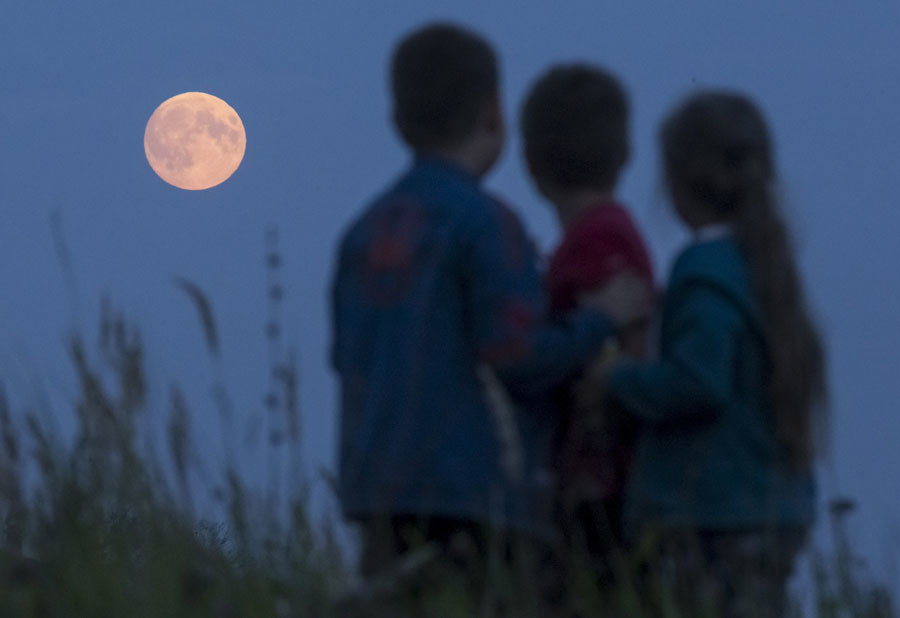Children look at the moon as they gather in the settlement of Poschupovo in Ryazan region, Russia, September 27, 2015. ©Maxim Shemetov