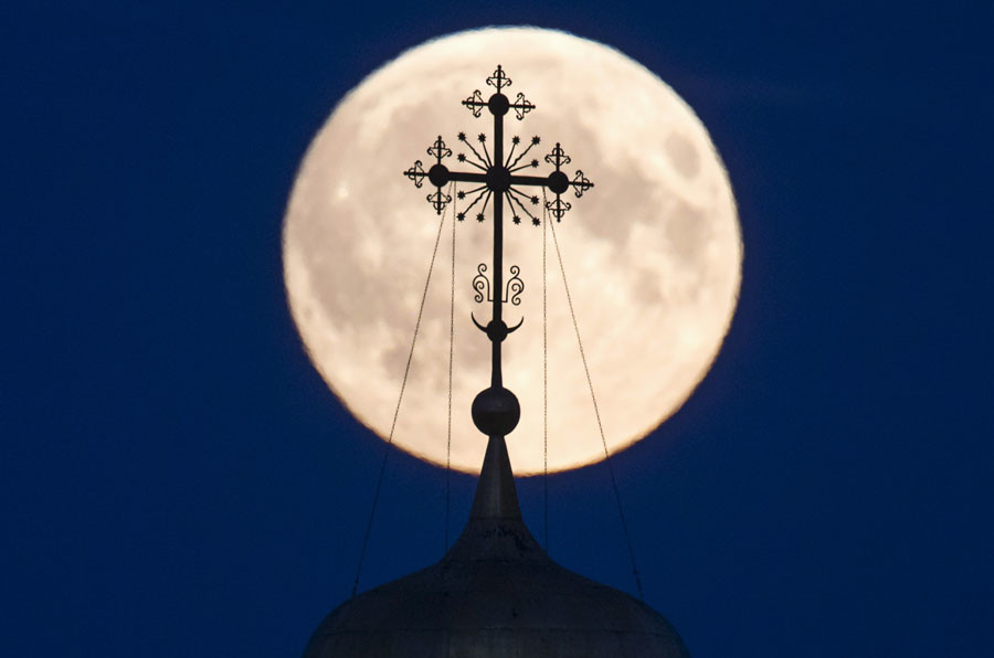 A cross atop of a local monastery is seen silhouetted against the moon in the settlement of Poschupovo in Ryazan region, Russia, September 27, 2015. © Maxim Shemetov