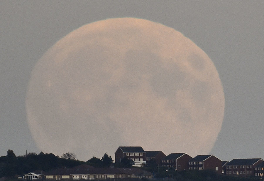 """A """"supermoon'' rises above Brighton in southern England September 27, 2015. © Toby Melville"""