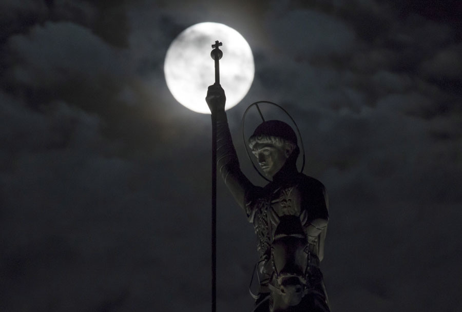 A monument to St. George the Victorious is seen silhouetted against the moon in Ryazan, Russia, September 27, 2015. © Maxim Shemetov