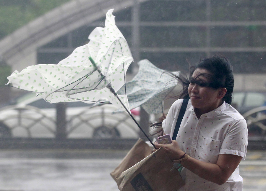 A woman holds onto her umbrella while walking against strong winds caused by Typhoon Dujuan in Taipei, Taiwan, September 28, 2015. © Pichi Chuang