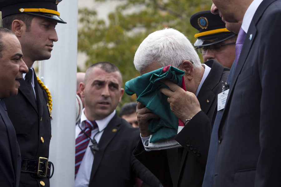 Palestinian President Mahmoud Abbas kisses a Palestinian flag before raising it during United Nations General Assembly at the United Nations in Manhattan, September 30, 2015. © Andrew Kelly
