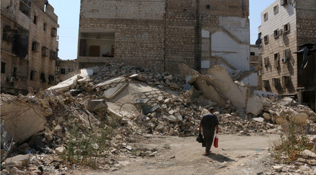 A man walks along a damaged street in the al-Katerji district in Aleppo, Syria. © Abdalrhman Ismail