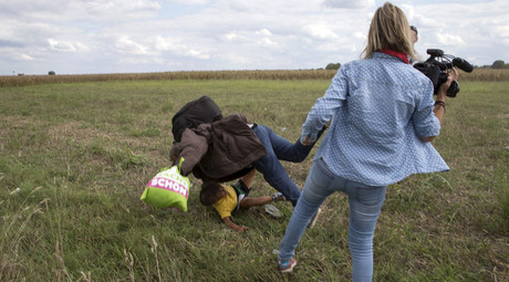 A migrant carrying a child falls after tripping on TV camerawoman (R) Petra Laszlo while trying to escape from a collection point in Roszke village, Hungary, September 8, 2015. © Marko Djurica