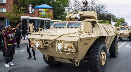 A man gestures as military vehicles drive on the streets of Baltimore, Maryland © Lucas Jackson
