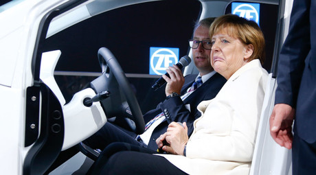 German Chancellor Angela Merkel reacts as she sits with German autoparts manufacturer ZF Friedrichshafen CEO Stefan Sommer inside a car as she makes an opening tour of the Frankfurt Motor Show (IAA) in Frankfurt, September 17, 2015. © Ralph Orlowski