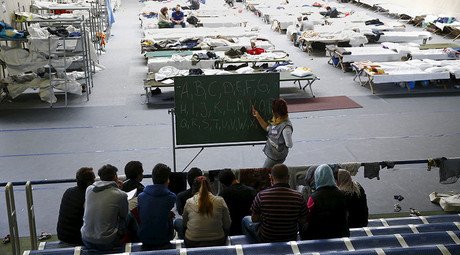 A volunteer points at a blackboard as migrants participate in a spontaneously organized English and German lesson at an improvised temporary shelter in a sports hall in Hanau, Germany, September 24, 2015 © Kai Pfaffenbach