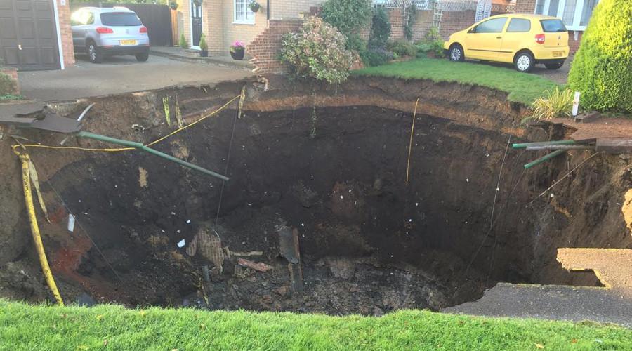 Massive sinkhole swallows suburban street, families evacuated