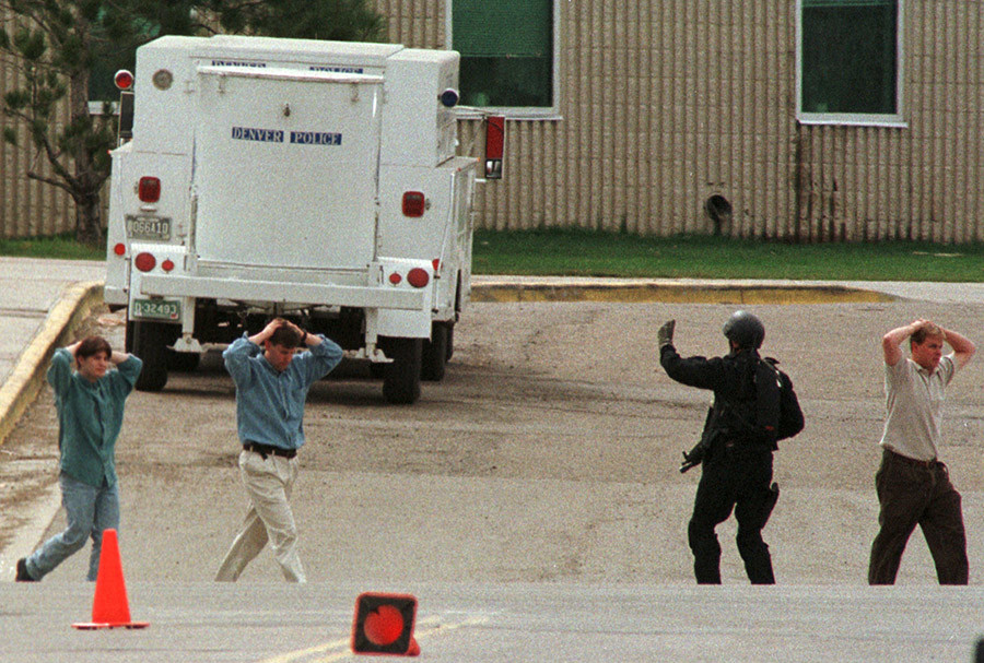 Columbine High School students are led from the building with an escort by a member of a SWAT team in Littleton, Colorado © Reuters