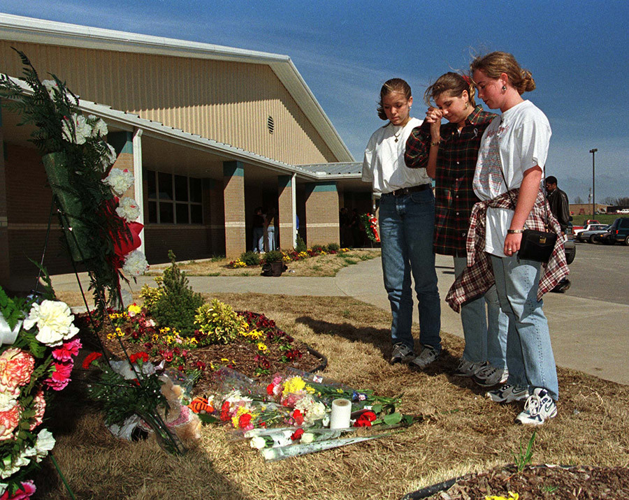 Local college students (L-R) Codi Allen, Cara Roop and Brandy Bell stand a makeshift memorial at the scene of Tuesday's school shooting at Jonesboro's Westside Middle School, March 25. © Reuters
