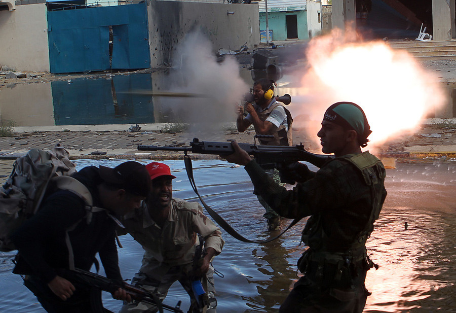 ARCHIVE PHOTO: Anti-Gaddafi fighters return fire during clashes with Gaddafi forces in Sirte October 15, 2011. © Asmaa Waguih