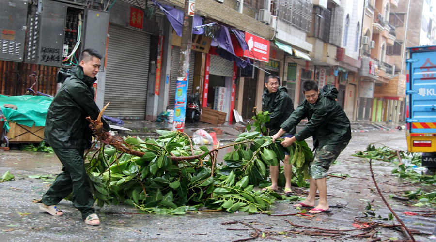 People try to remove a bough from a street as Typhoon Mujigae hits Maoming, Guangdong province, October 4, 2015. © Stringer
