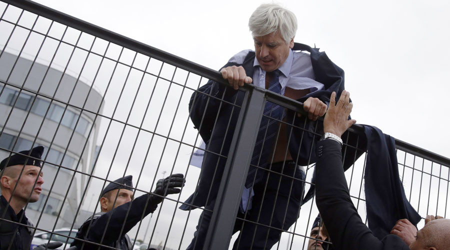 Director of Air France in Orly Pierre Plissonnier, nearly shirtless, tries to cross a fence, helped by security and police officers, after several hundred of employees invaded the offices of Air France, interrupting the meeting of the Central Committee in Roissy-en-France, on October 5, 2015. © AFP