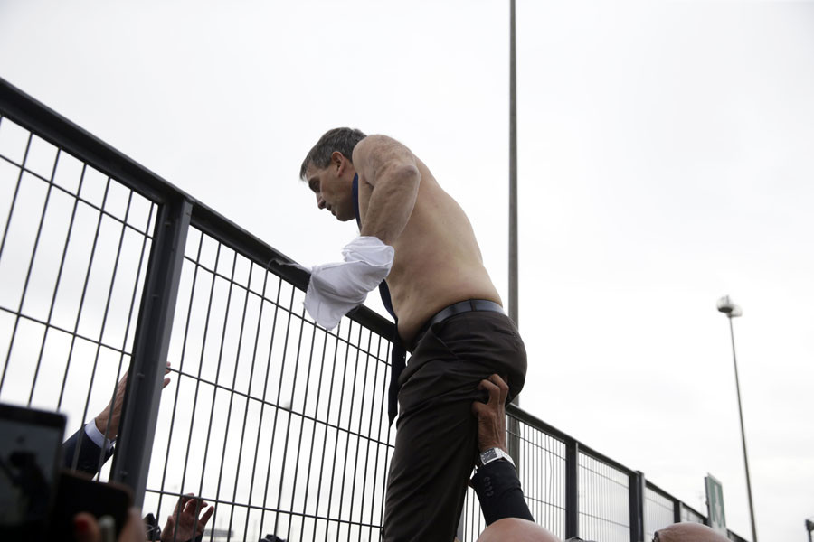 Human Resources Director of Air France Xavier Broseta, shirtless, tries to cross a fence, after several hundred of employees invaded the offices of Air France, interrupting the meeting of the Central Committee (CCE) in Roissy-en-France, on October 5, 2015. © AFP