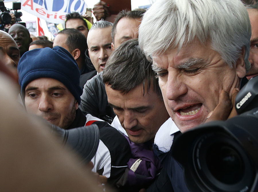 Xavier Broseta (C), Executive Vice President for Human Resources and Labour Relations at Air France, and Pierre Plissonnier (R), Air France deputy of long-haul flights, are surrounded by employees at the Air France headquarters building near Paris, France, October 5, 2015. © Jacky Naegelen