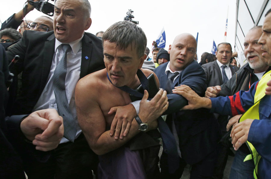 A shirtless Xavier Broseta, Executive Vice President for Human Resources and Labour Relations at Air France, is evacuated by security after employees interrupted a meeting with representatives staff at the Air France headquarters near Paris, France, October 5, 2015.© Jacky Naegelen