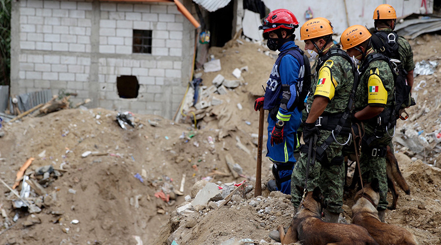 Mexican Army rescue team members and sniffer dogs survey an area affected by a mudslide in Santa Catarina Pinula, on the outskirts of Guatemala City, October 4, 2015. © Josue Decavele