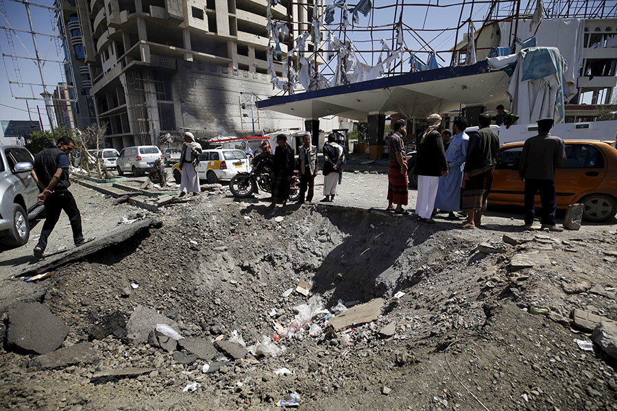 People gather at the site of a Saudi-led air strike that targeted the Complex for Automotive Services near a tunnel leading to the presidential house in Yemen's capital Sanaa, October 1, 2015. © Mohamed al-Sayaghi