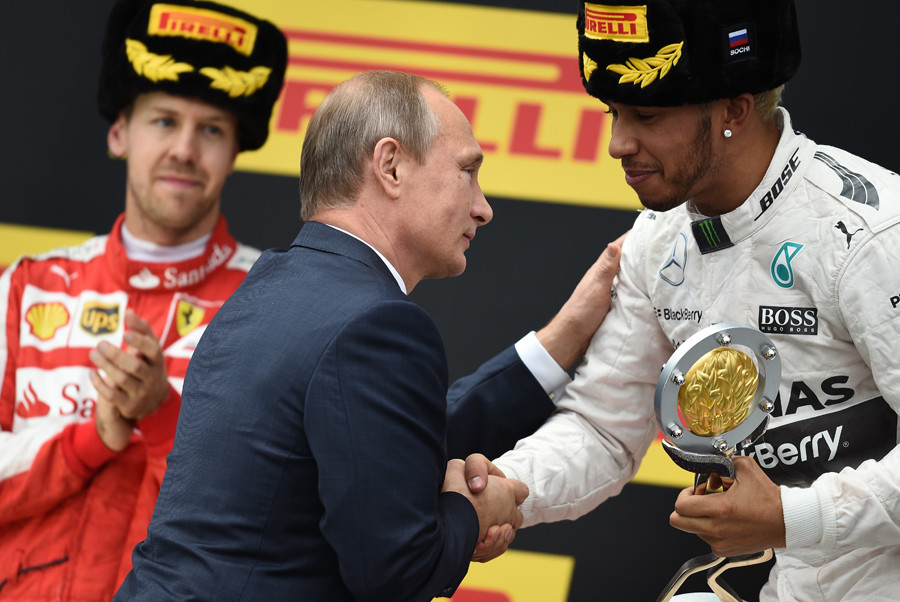 Russian President Vladimir Putin, center, hands the F1 Russian Grand Prix cup to Mercedes' Lewis Hamilton, right, who took the 1st place at the F1 Russian Grand Prix, at the award ceremony, October 11, 2015. Left: Ferrari's Sebastian Vettel, who took the 2nd place. © Alexey Filippov