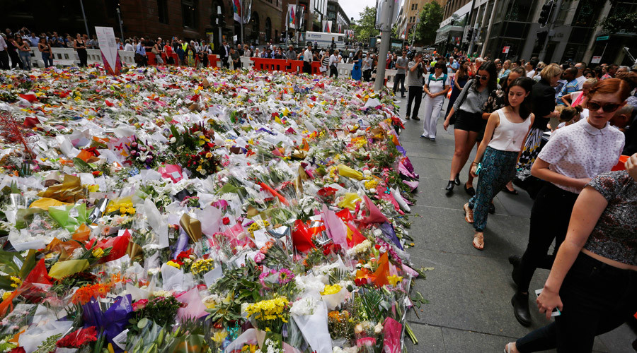 Members of the public observe the thousands of floral tributes left near the site of the Sydney cafe siege in Martin Place December 17, 2014. © Jason Reed