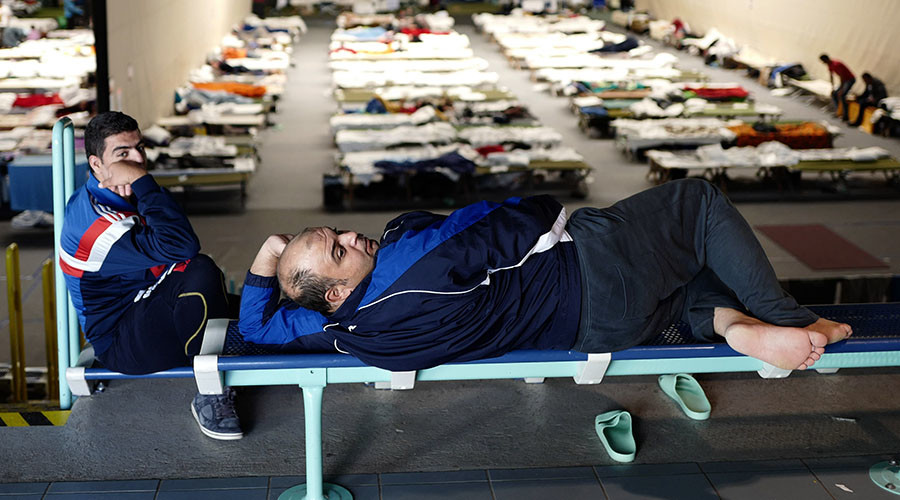 Refugees rests at an improvised temporary shelter in a sports hall in Hanau, Germany. © Kai Pfaffenbach
