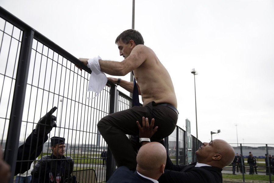 Air France Executive Vice President in charge of Human Resources and Labour Relations Xavier Broseta tries to cross a fence, helped by security and police officers, after several hundred employees stormed the offices of Air France on October 5, 2015. © Kenzo Tribouillard