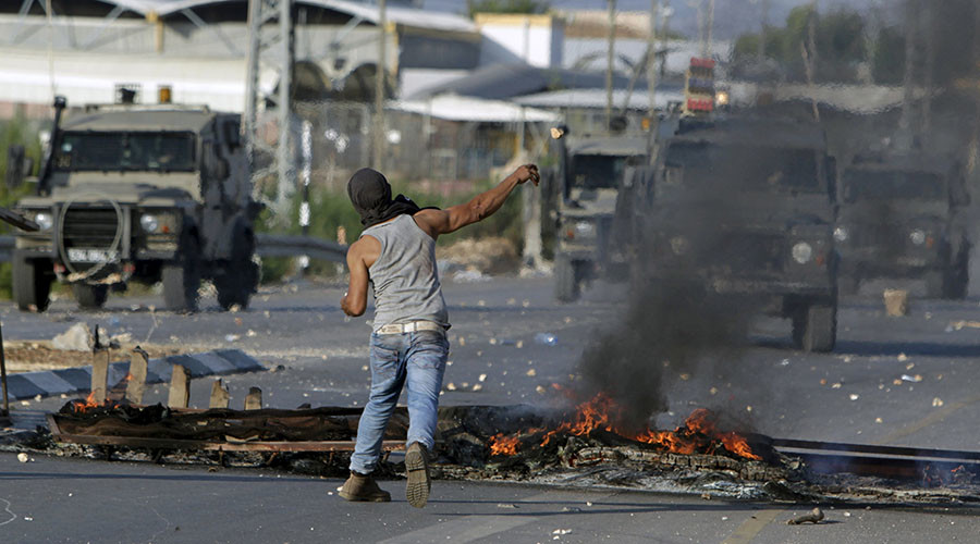 © A Palestinian protester hurls stones towards Israeli troops during clashes in the West Bank city of Jenin October 16, 2015. © Mohammed Ballas