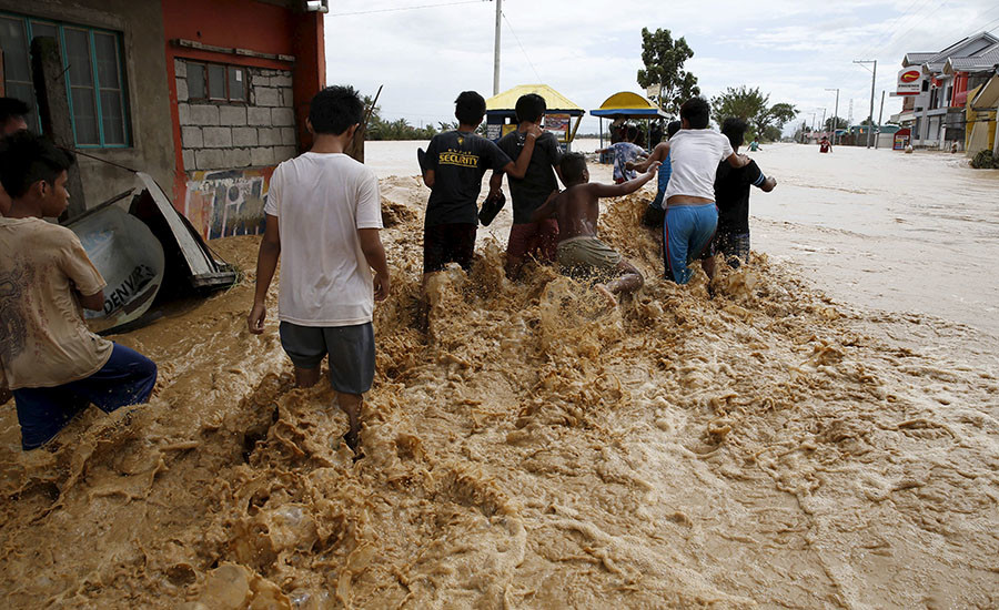 Residents wade along a flooded road amidst a strong current in Sta Rosa, Nueva Ecija in northern Philippines October 19, 2015, after it was hit by Typhoon Koppu. © Erik De Castro