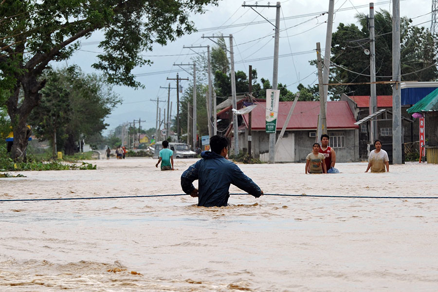 A resident holds onto a rope as he negotiates a flood current along a submerged highway in Santa Rosa town, Nueva Ecija province, north of Manila on October 19, 2015, a day after typhoon Koppu hit Aurora province. © Ted Aljibe