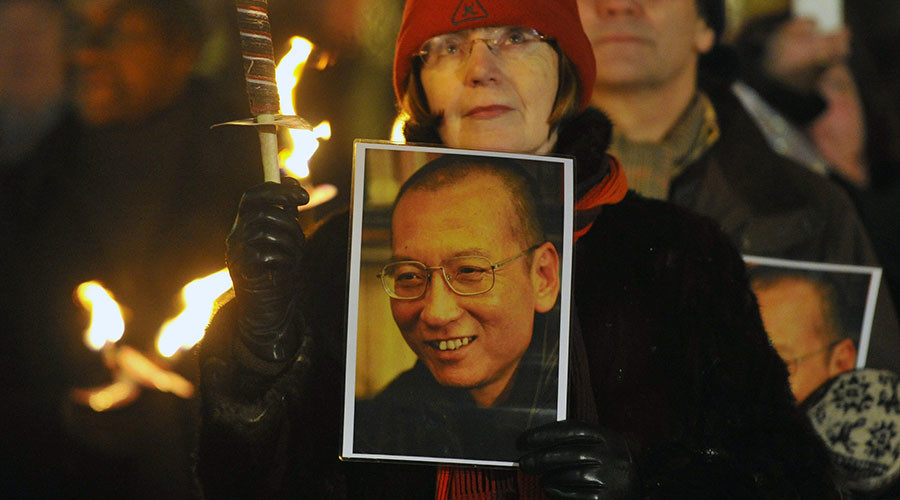 A woman holds a photograph of Liu Xiaobo during a torchlit procession in the centre of Oslo following the Nobel Peace Prize ceremony December 10, 2010. © Toby Melville