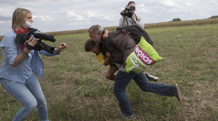 A migrant runs with a child before tripping on TV camerawoman Petra Laszlo (L) and falling as he tries to escape from a collection point in Roszke village, Hungary, September 8, 2015. © Marko Djurica